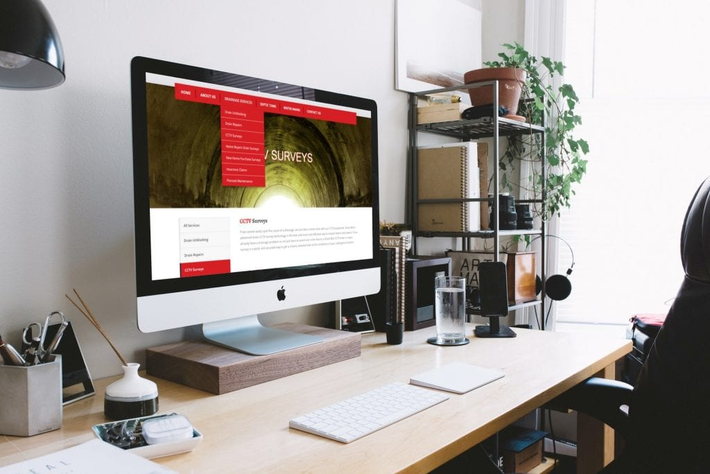 An Apple computer in a bright modern office showing the DrainBlitz website