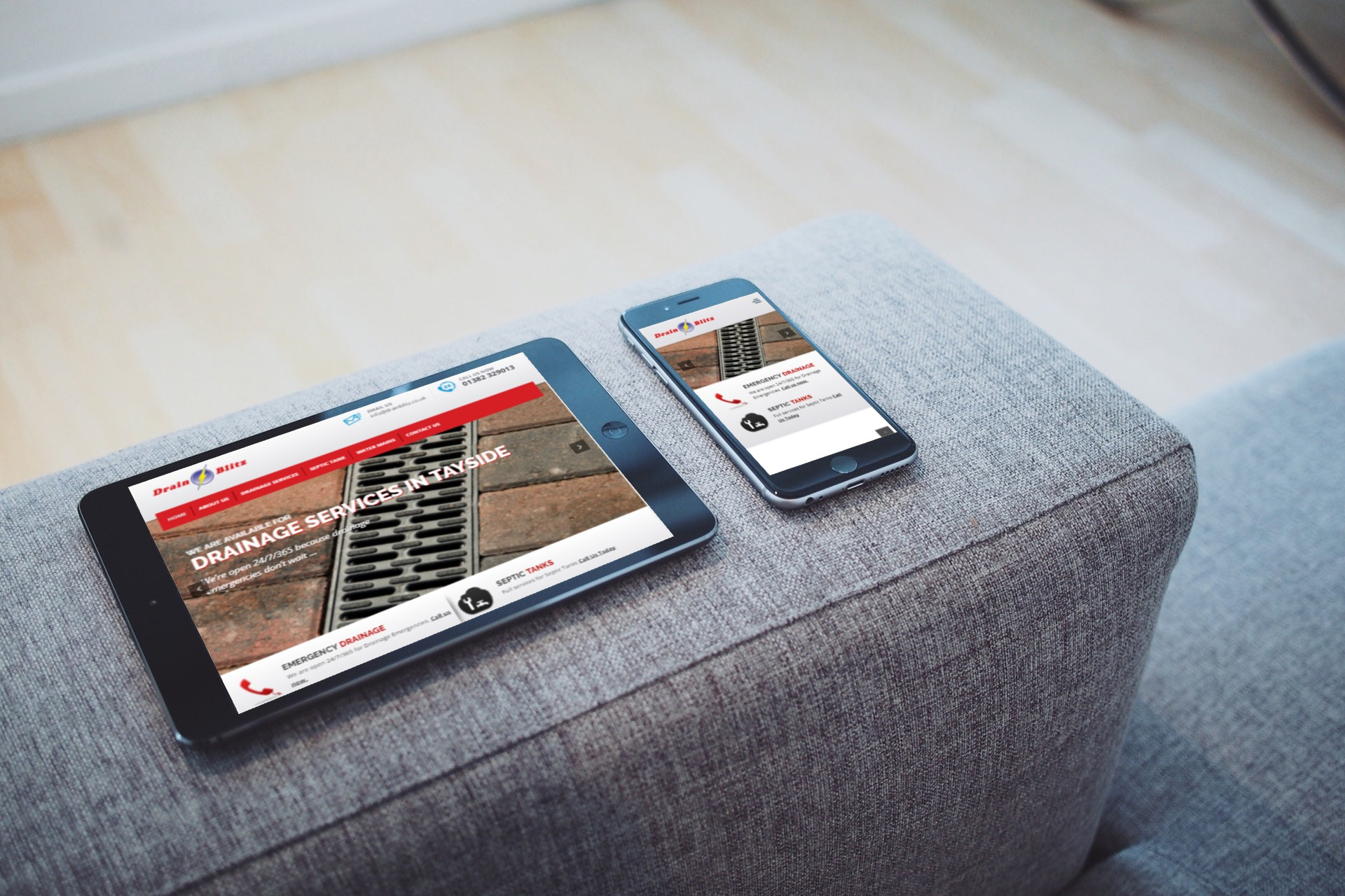 A tablet and phone sitting on the arm rest of a modern grey sofa displaying the DrainBlitz website