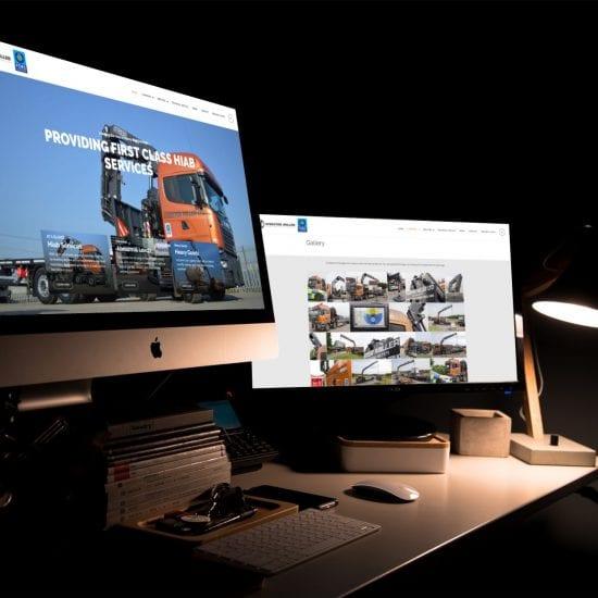 Multiple monitors on a desk in a dark room showing the Webster Miller website