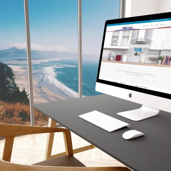 An Apple computer in a modern office showing the WRG Gas website with a scenic background visible through large glass panes