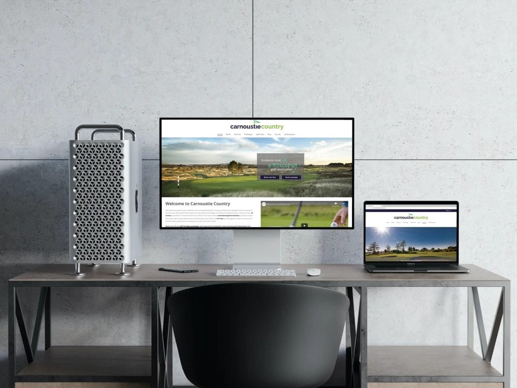 A computer monitor and laptop screen in a stark modern office showing the Carnoustie Country website