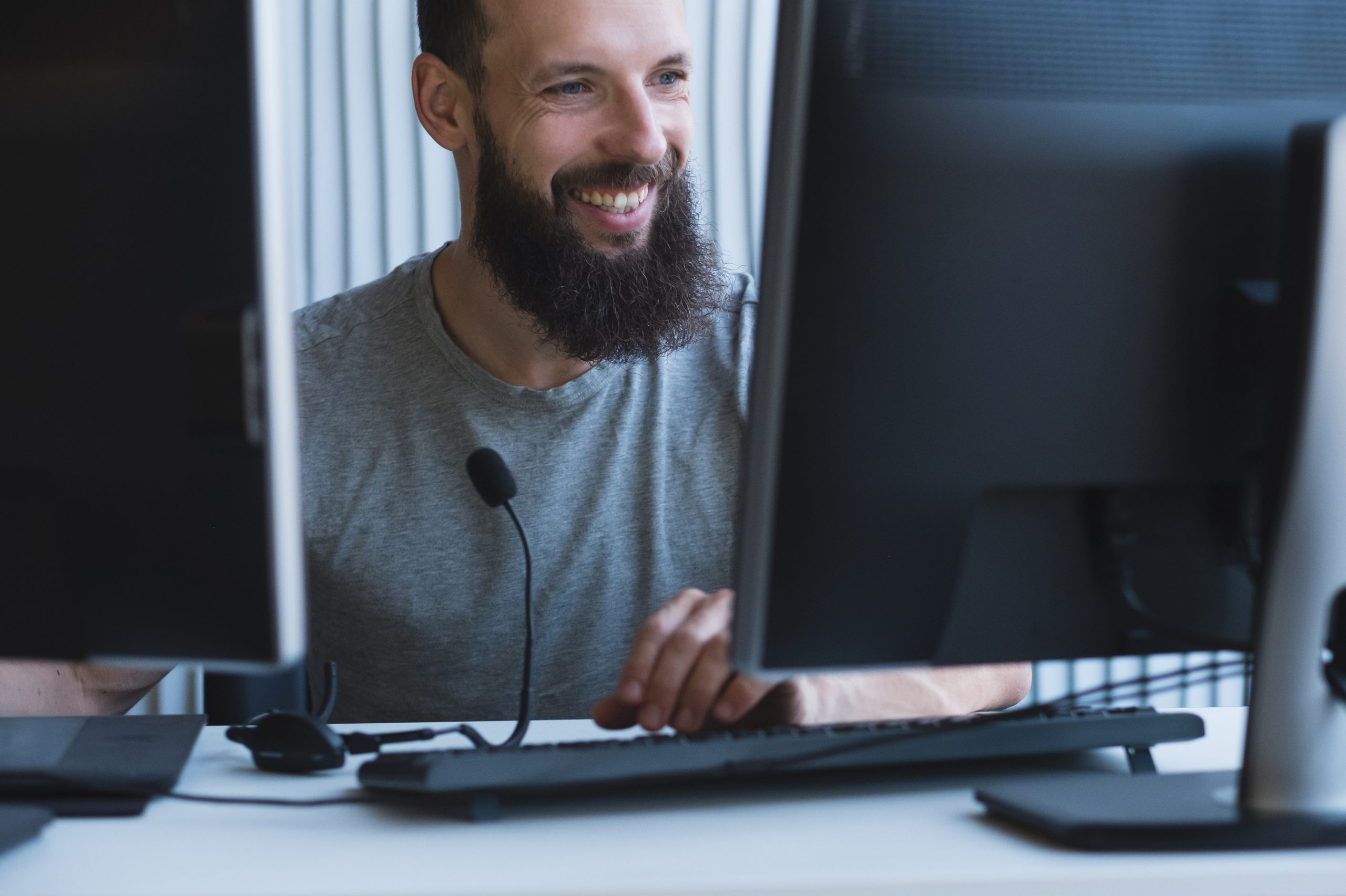 A male IT technician in front of two computer monitors phoning a customer