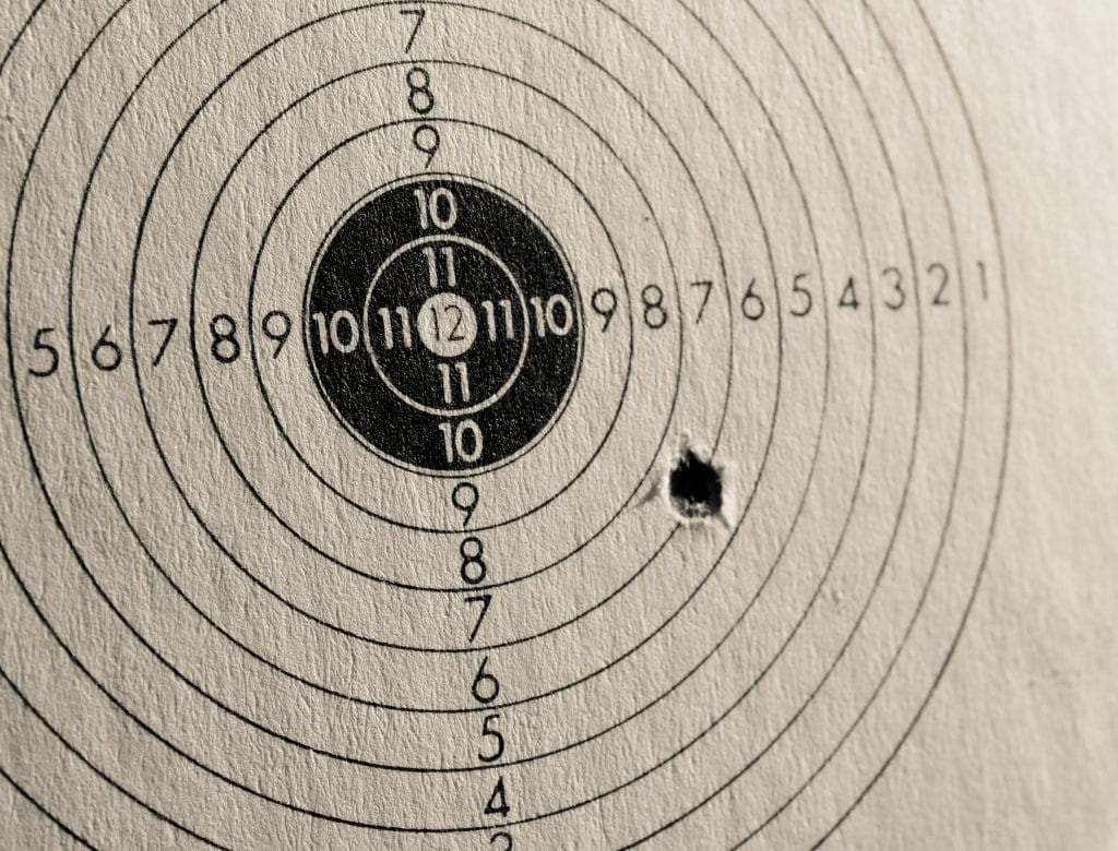 Photograph of a target sheet. Practice shot hit wide at a 7.