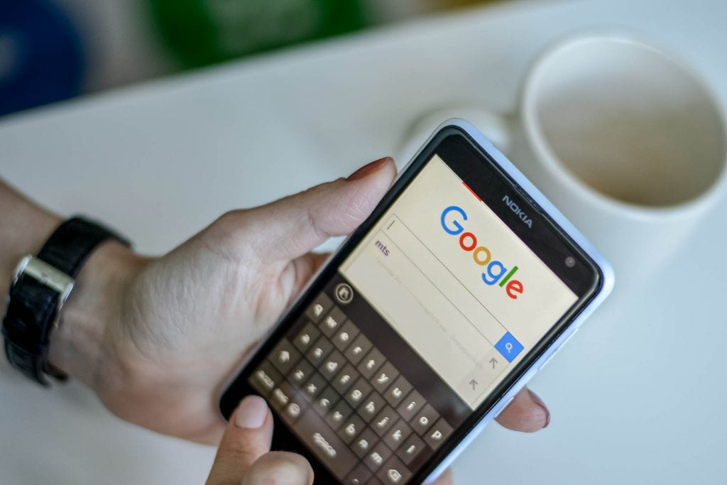 Someone using a mobile phone to search Google